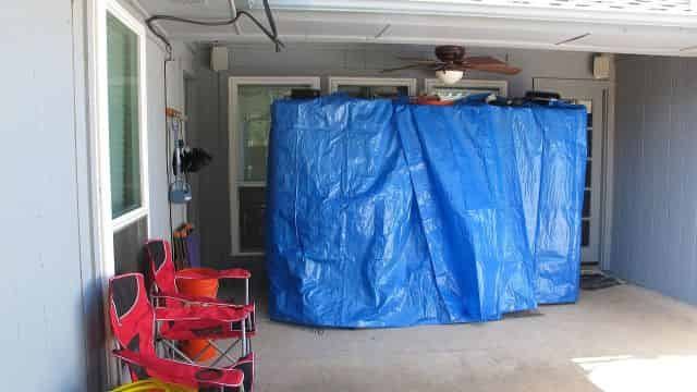 Shelves full, covered in tarps on the patio